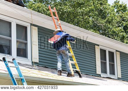 Man Walking On A Residential Roof Carrying A Package Of Shingles Between Two Ladders To Replace The