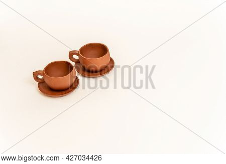 Two Empty Small Brown Clay Cups With Handles On Saucers