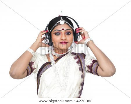 Female Odissi Dancer Of Indian Origin Enjoying Music