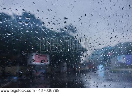 Image Shot Through Raindrops Falling On Wet Glass, Abstract Blurs Of Traffic - Monsoon Stock Image O