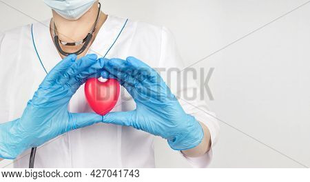 Doctor Cardiologist Hands With Heart. Close-up View Of Heart In Hands With Gloves Of Doctor Wearing