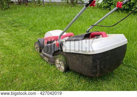 Lawn Mower Cutting Green Grass In Backyard. Lawn Mower On Fresh Green Lawn.