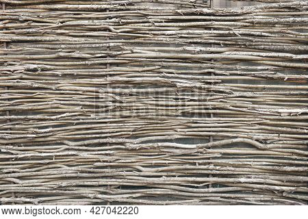 Wattle Fence Of Dry Horizontal Twigs As The Background. Traditional Rustic Fence. Abstract Wooden Ba
