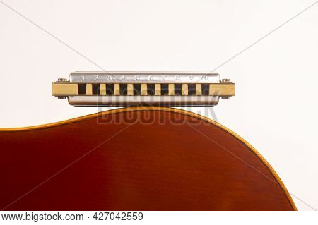 The Harmonica Rests On The Body Of A Classical Guitar. Classical Musical Wind Instrument.