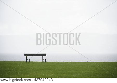 Lonely Empty Bench In Open Tranquil Landscape By The Sea For Mindfulness And Meditation