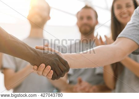 Close Up. Handshake Of Two Students On The Background Of The St