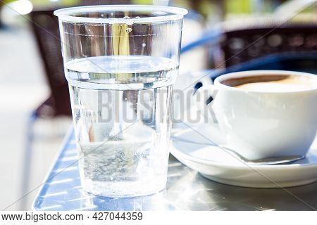 Transparent Plastic Glass With Water With Cup Of Cappuccino And Caffe Tables In Background Blurred.
