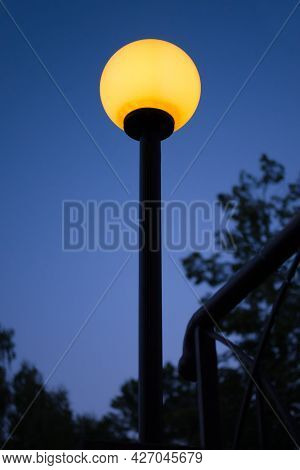 Street Lamp With Bright Yellow Light Against The Evening Deep Blue Sky. Bright Sphere Shape Outdoor