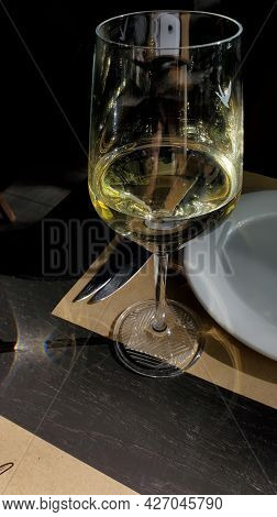 Closeup Of Transparent Wine Glass On Tabletop. Glassware For White Wine In Front Of Window. Alcohol
