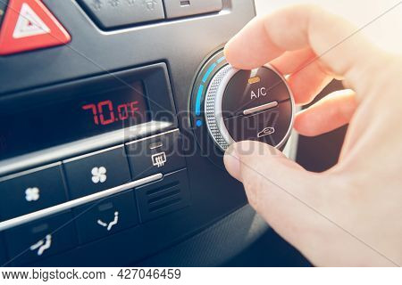 Man Hand Set The Comfortable Temperature In Fahrenheit Of Air Conditioner In The Car. Driver Turning