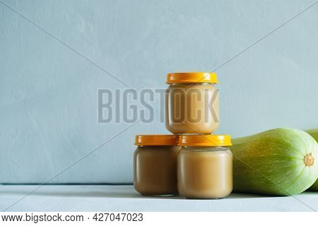 Baby Food, Childrens Complementary Food, Canned Goods Concept. Three Jars Of Zucchini Puree And Zucc