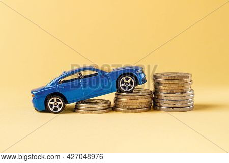 Blue Toy Car Rides Up A Stack Of Coins Against Yellow Background. Concepts Of Costs Of Car Insurance