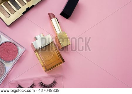 Decorative Cosmetics On A Pink Background. Focus On Lipstick And Perfume. False Eyelashes, Eye Shado