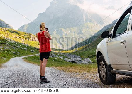 Young Caucasian Woman In Shorts Taking Pictures On A Mountain Near Her White Off-road Car During An