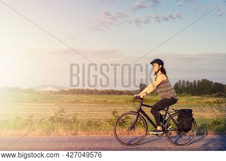 Adventurous White Cacasusian Woman Riding A Bicycle On A Road. Sunny Summer Sunset. Barnston Island,