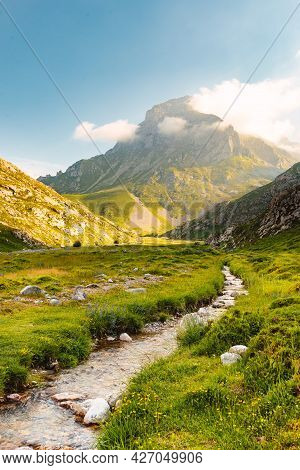 Vertical Landscape Photography With A Small River And Mountains In The Background On A Sunny Day At