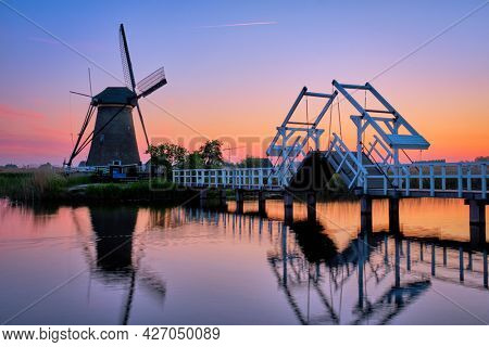 Netherlands rural lanscape with windmills and bridge at famous tourist site Kinderdijk in Holland in twilight