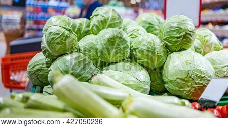 Young cabbage ans zucchini in shop. Green vegetables sold on grocery market. Natural organic veggies at supermarket. Vegetarian healthy nutrition