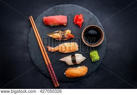 Tasty sushi sashimi set composition with shrimps, ginger and soy sauce served with chopsticks and green wasabi on black plate on table from above. Traditional asian food with rice and seafood