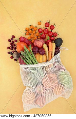 Healthy fruit and vegetables in a net shopping bag high in lycopene for a healthy heart and to lower blood pressure, high in antioxidants, anthocyanins, vitamins, minerals and dietary fibre. Top view