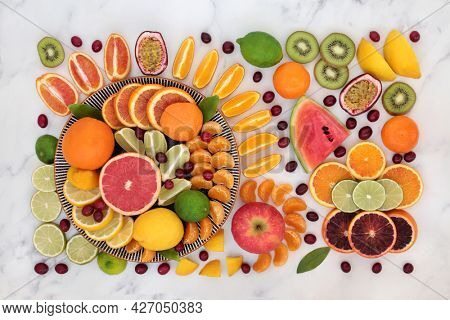 Tropical and citrus fruit for immune system boost high in antioxidants, fibre, anthocyanins, lycopene, vitamins and minerals. Natural healthcare concept.  Flat lay on marble.