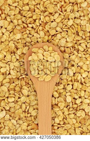 Roasted fava beans for a healthy vegan and vegetarian diet snack in a wooden spoon forming a background. High in protein, vitamins, dietary fibre and nutrients. Flat lay, top view.