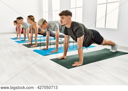 Group of young hispanic people concentrate training at sport center