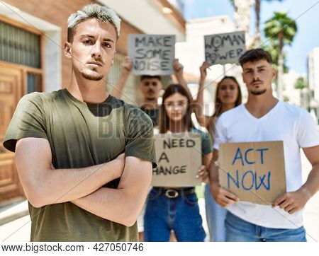 Young hispanic activist man with arms crossed gesture standing with a group of protesters holding banner protesting at the city.