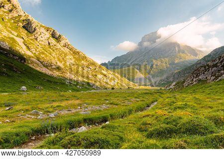 Landscape Photography With A Small River And Mountains In The Background On A Sunny Day. Picos De Eu