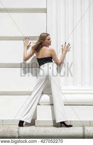 Full body portrait of a young beautiful blonde girl in white trousers