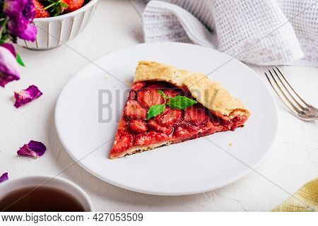 Slice Of Vegetarian Fresh Baked Strawberry Galette With Mint Leaves On White Plate