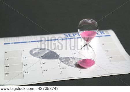 Hour Glass Standing On Top Of Calendar On Black Tabletop Background. Copy Space.