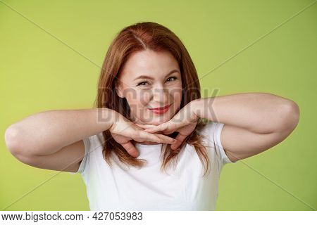 Aging, Cosmetology, Wellbeing Concept. Happy Self-assured Redhead Woman Hold Hands Under Jawline Smi