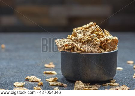 Dry Muesli In A Saucer On The Background Of A Stone Table Top. Healthy Food And Light Diet Breakfast