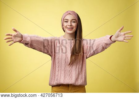 Attractive Friendly Positive Young European Woman Wearing Sweater, Headband Welcoming Extanding Arms