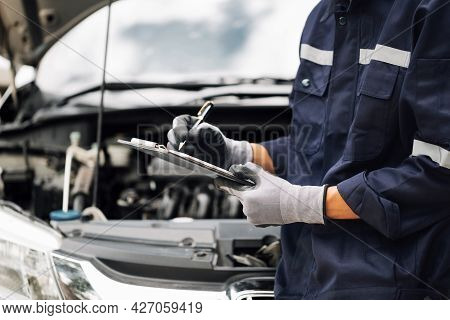 Car Service, Repair, Maintenance Concept,auto Mechanic Man Or Smith Writing To The Clipboard At Work