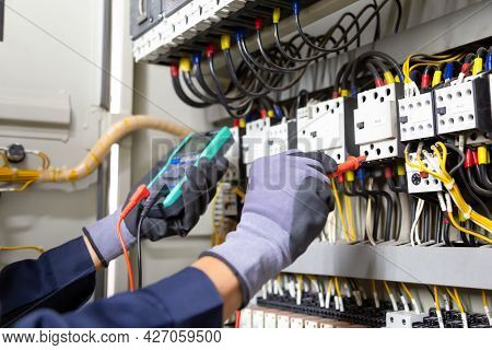 Electrician Engineer Tests Electrical Installations And Wires On Relay Protection System. Adjustment