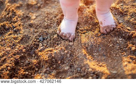 Children's Bare Feet In Summer On A Golden Sandy Beach Close-up. The Concept Of Child Safety. The Co