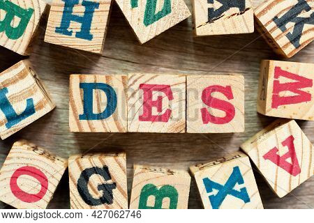Alphabet Letter Block In Word Des (abbreviation Of Delivered Ex Ship) With Another On Wood Backgroun