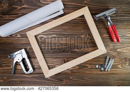 Photo On Canvas In Roll, Canvas Stretcher, Stapler And Stretching Tool On Brown Wooden Background