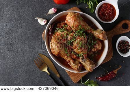 Georgian Meat Dish Chashushuli With Chicken And Tomato On Wooden Board On Dark Gray Table. View From