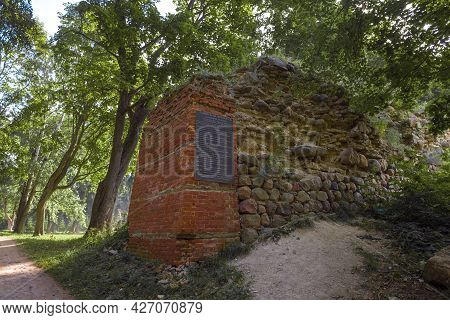 Gdov, Russia - July 19, 2020: Ruins Of A Defensive Wall With A Memorial Plaque On A Sunny July Day.