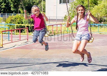 Two Friendly Sisters Swing With Pleasure On A Walk In The Playground.