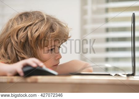 Portrait Of Concentrated Kid Surfing The Internet In School. Young Happy Schoolboy Using Computer. C