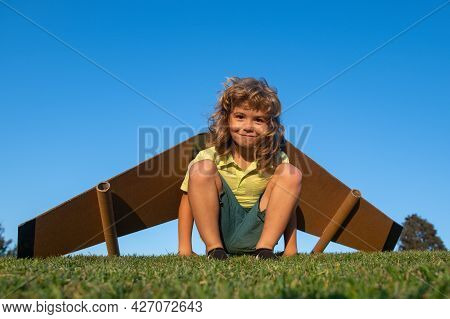 Cute Dreamer Boy Playing With A Cardboard Airplane On Grass. Childhood. Fantasy, Imagination.