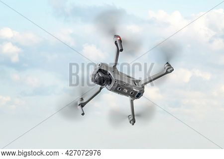 A Flying Quadcopter Is On A Blue Background.