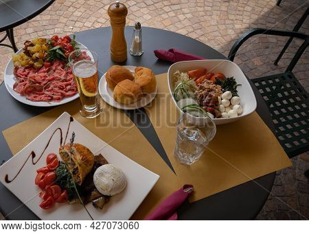 Laid Table With Carpaccio, Vegetable Pie And Salad