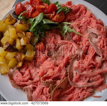 Roast Beef With Lettuce, Cherry Tomatoes And Fried Potatoes On A Large White Platter