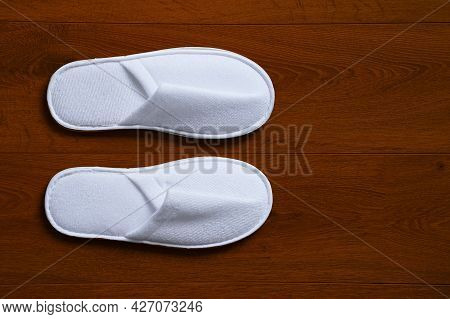 A Pair White Slippers, Isolated On Wooden Floor. Top View Of A Pair Of New Soft White Slippers In Th