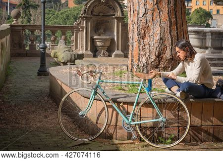 Viterbo, Italy - February 23, 2021, Young Woman With An Old Bike Resting In A Square In Viterbo, Ita